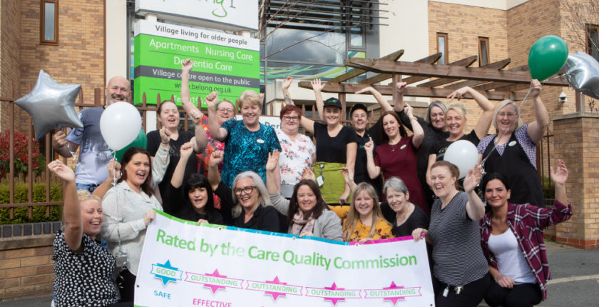 Belong Wigan team with CQC outstanding banner